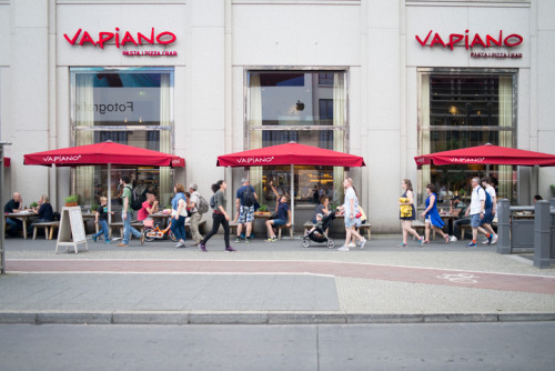 Central Berlin, Germany - July 08, 2017: a franchise fast food restaurant Vapiano at Potsdamer Platz in summer. People sitting and enjoy their food.